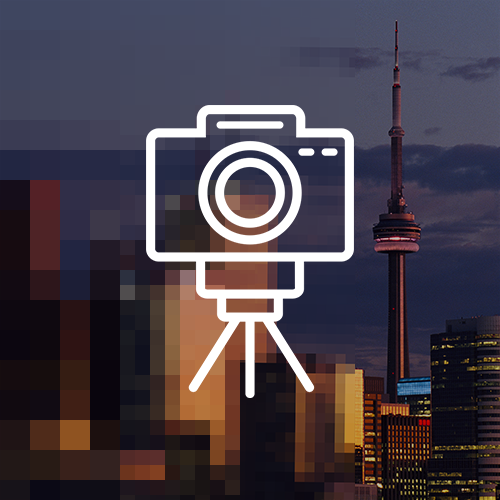 Pixelated image of downtown Toronto and CN Tower during sunset. White icon of camera on tripod overlay.