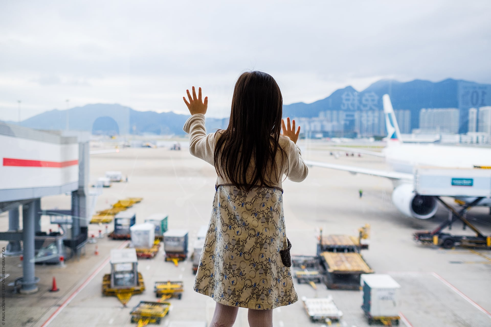 Girl touching window and looking at planes at Hong Kong International Airport.