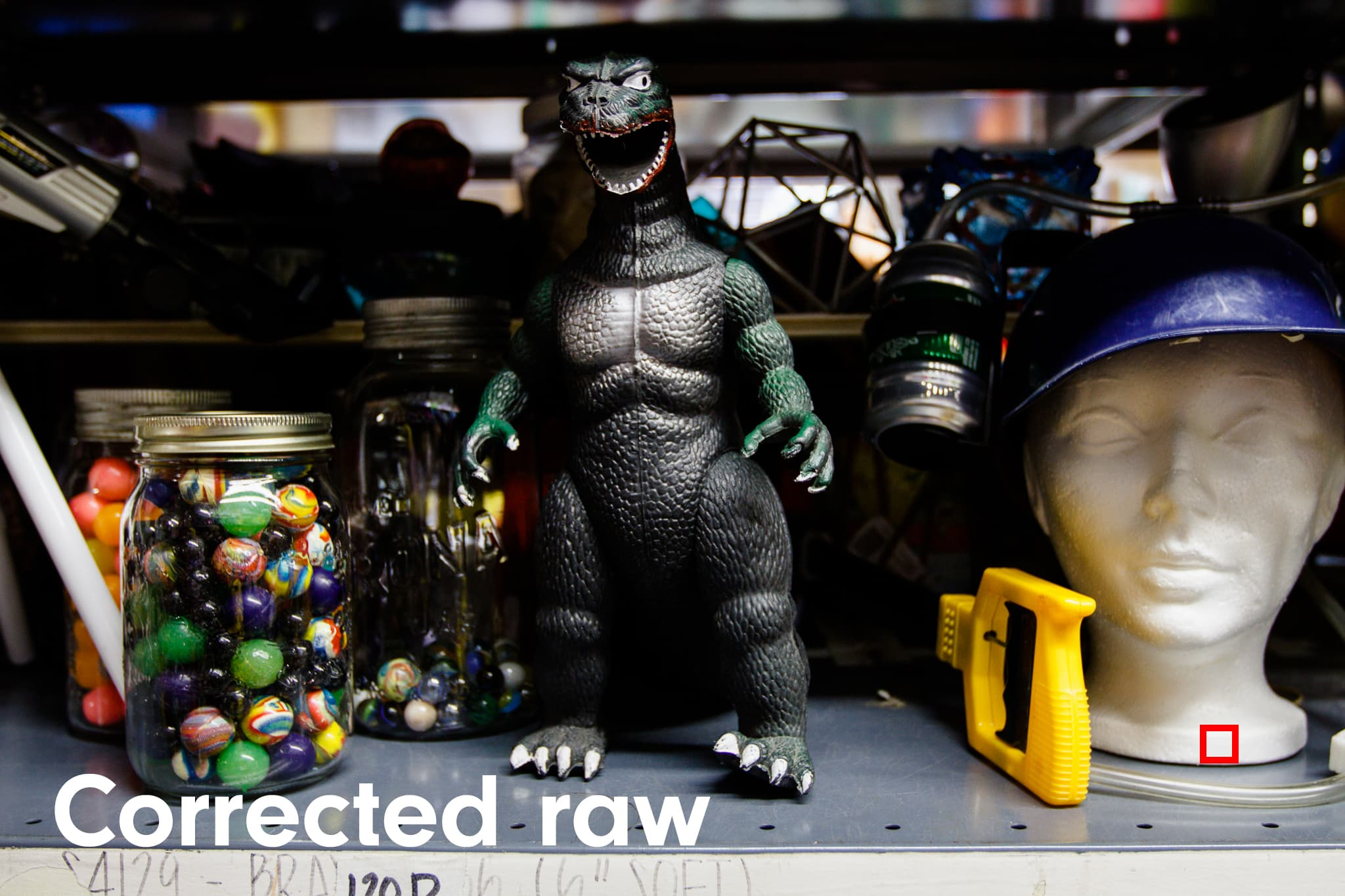 Godzilla toy in craft shop showing raw file whose white balance was corrected.